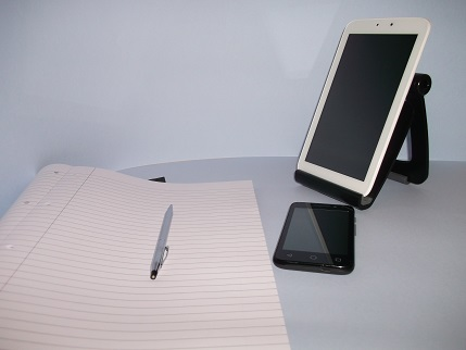 Still life photo of pen and paper, tablet and mobile phone